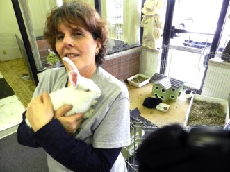 A white woman with short brown hair stands in front of a fenced off area for bunnies, holding a fluffy white bunny in her arms
