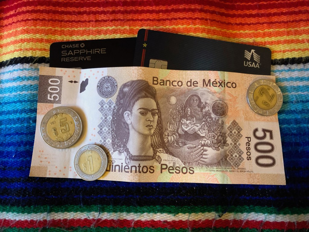 A debit card and credit card partly covered by a 500 peso note held down by several peso coins. All laying on a multi colored mexican blanket.