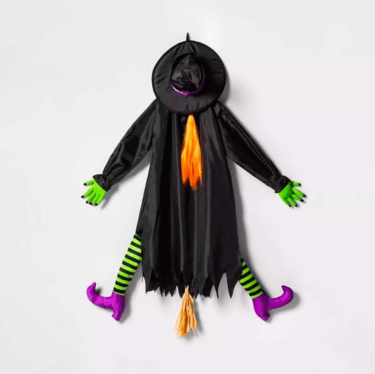 A cloth figure of a witch wearing green and black striped tights that looks like it's crashing into a wall.