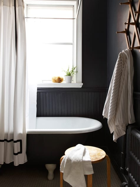 """Image above: Black can be imposing and creepy, but also calming and serene. What a perfect space for a bubbly bath. That curtain is a bit """"Psycho"""" though, no?"""
