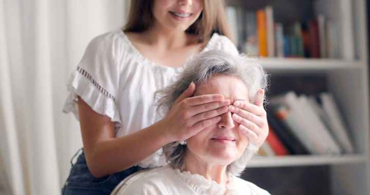 cheerful teenager playing with grandmother guess who game while making surprise in light living room