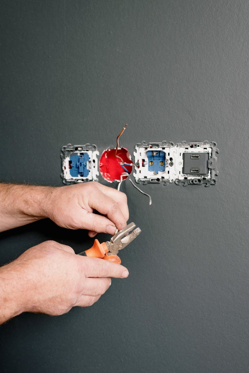 man repairing sockets and switches in room