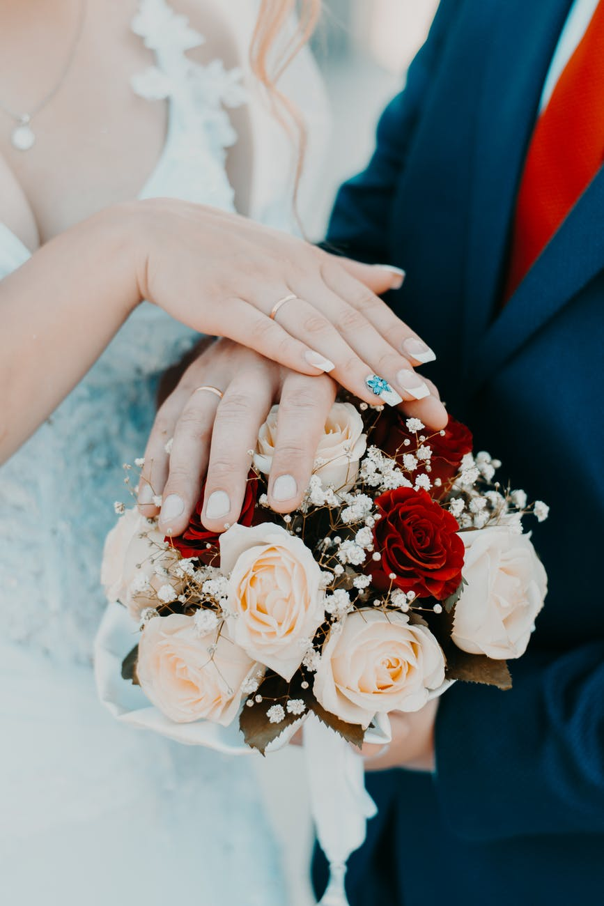 person holding bouquet of white nad red rose
