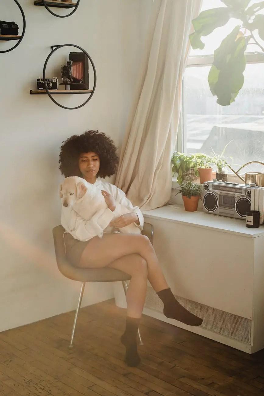 cheerful black woman sitting near window with dog