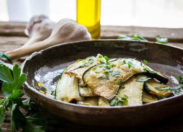 Italian marinated zucchini in a bowl with chopped parsley and garlic, a bottle of oil in the background