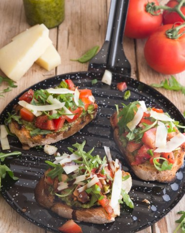 bruschetta made on a black round grill pan with tomatoes, parm and pest in the background