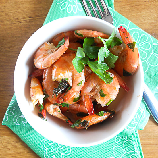 sauteed shrimp in a white bowl on a green napkin