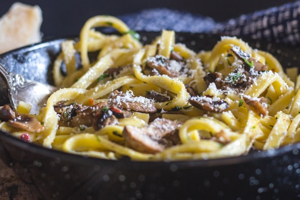 mushroom pasta in a pan sprinkled with parmesan cheese