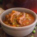 Italian beef stew in a grey bowl with a slice of crusty bread