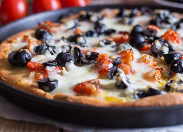 black olive pizza in a black pizza pan
