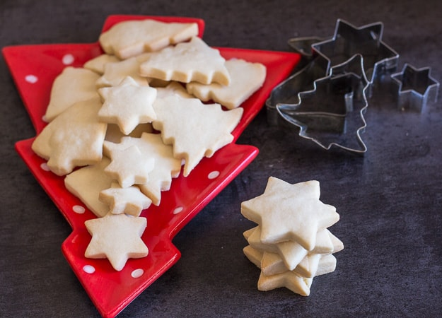 shortbread cookies one on top of each other and some on a christmas tree plate
