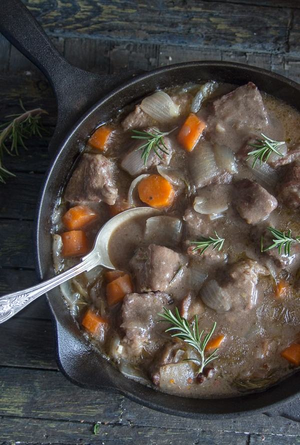 beef with white wine sauce in a black saucepan