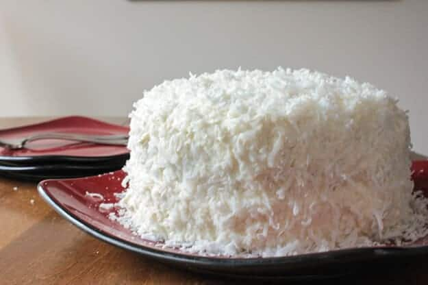 Coconut Cake, a delicious soft, moist cake with a creamy cream cheese frosting. Topped with coconut flakes, a perfect Christmas dessert.