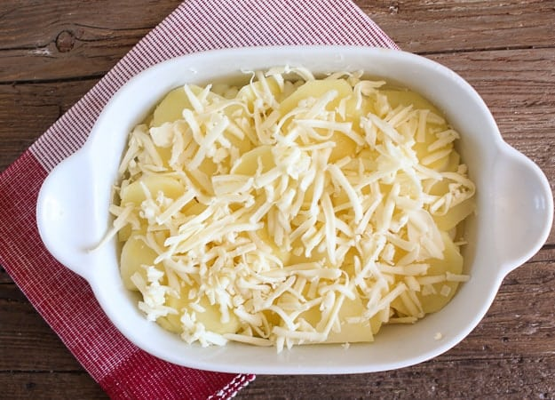 shredded cheese on the sliced potatoes for cheesy scalloped potatoes