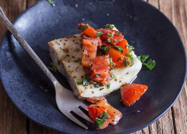 a piece of fish marinara on a black plate