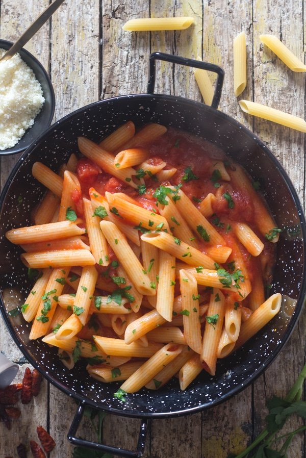 penne arrabbiata in a black pan on a wooden board