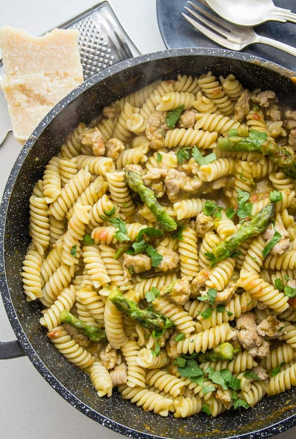 penne pasta with cut asparagus and sausage pieces in an asparagus cream sauce in a black skillet