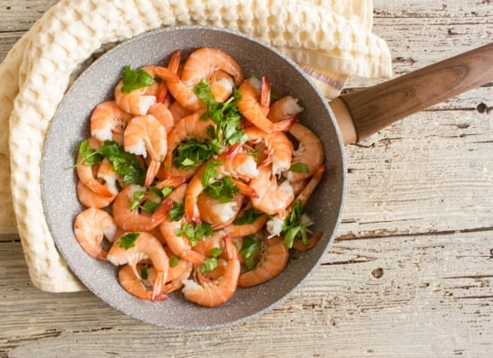 cooked sauteed shrimp in a pan on a yellow napkin
