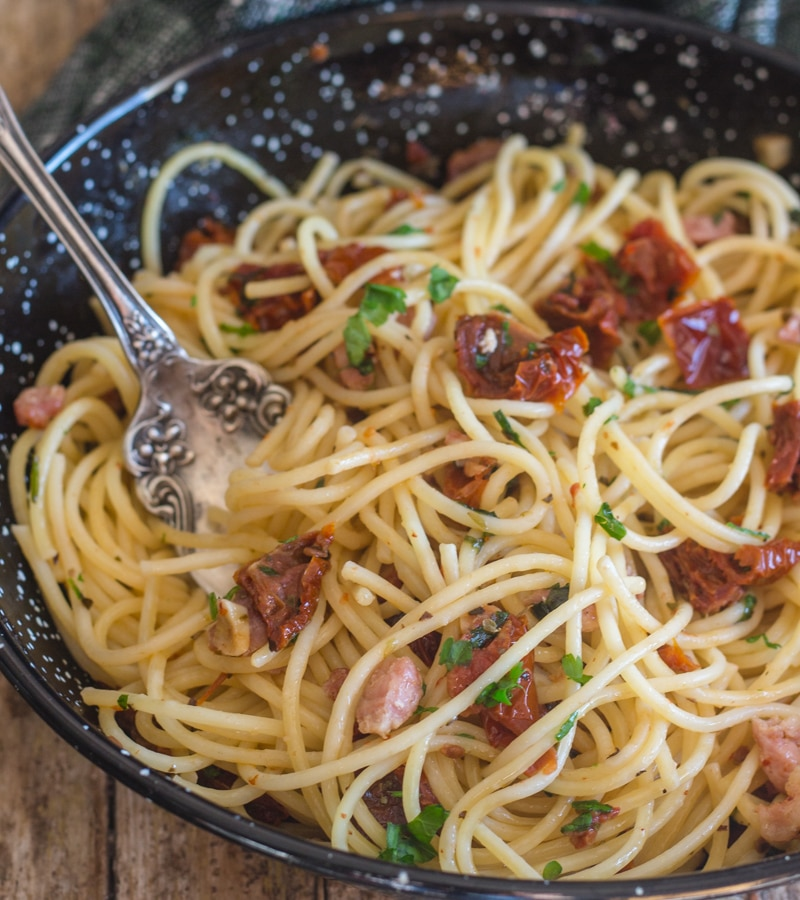 pasta in a black pan with sundried tomatoes and pancetta