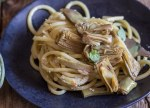 up close artichoke pasta on a black plate