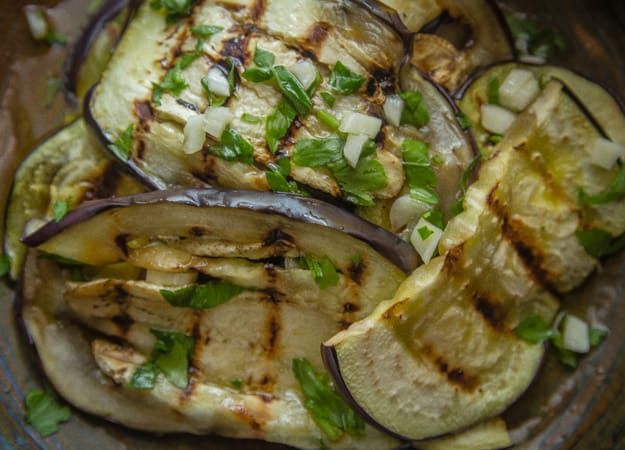 grilled eggplant with chopped garlic, parsley and olive oil in a bowl