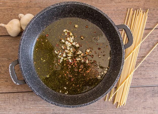 spaghetti aglio, olio e peperoncino in a pan with olive oil
