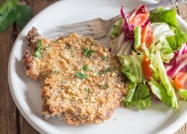 baked pork chops on a white plate with some salad