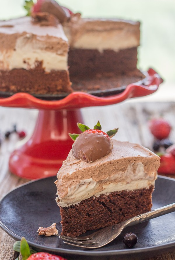 double chocolate mousse cake on a cake stand with a slice on a plate