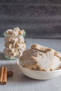 cinnamon sugar cookies in a bowl with 2 sticks of cinnamon beside it