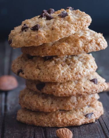 6 amaretti cookies stacked on one another on a blue board with almonds scattered