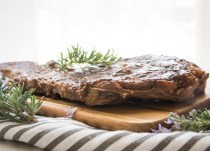 side view of grilled steak and rosemary on a wooden board