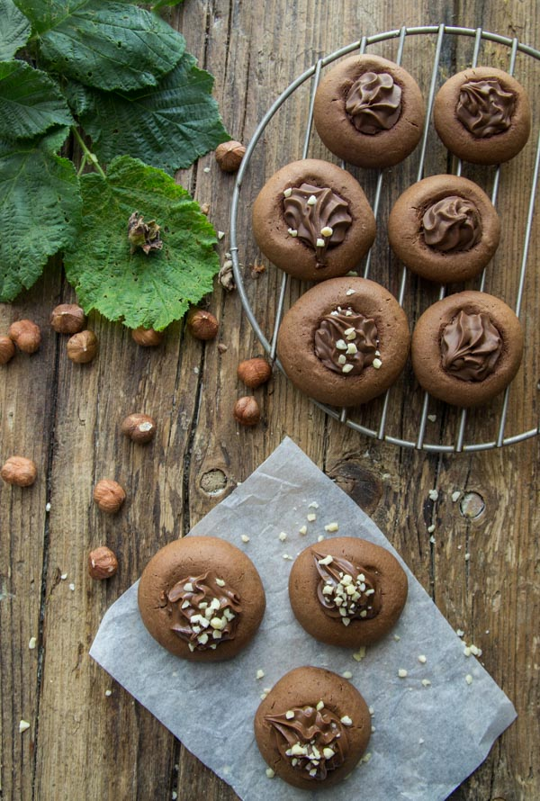round cookies filled with nutella, on a wooden board with whole hazelnuts