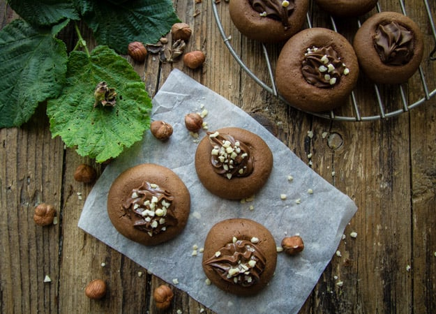 nutellotti cookies on a wooden board with chopped nuts on top