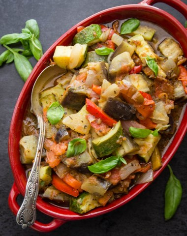 cooked ratatouille in a red oblong casserole serving dish with a silver spoon and basil leaves