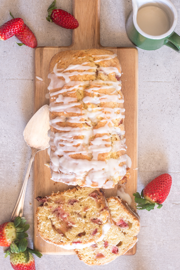 strawberry bread on a board with two slices cut