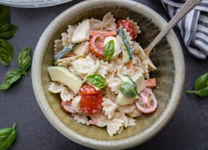 creamy italian pasta salad in a ceramic bowl with a fork.