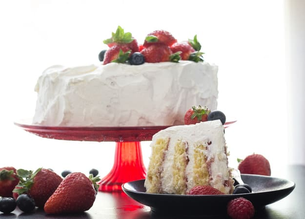 vertical layer cake on a red stand with a slice on a plate