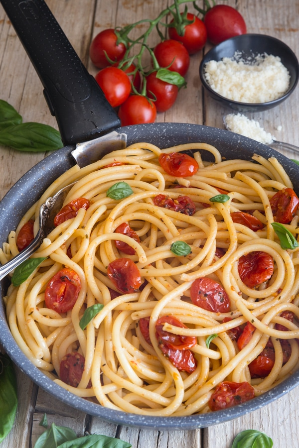 roasted tomatoes and bucatini in a pan