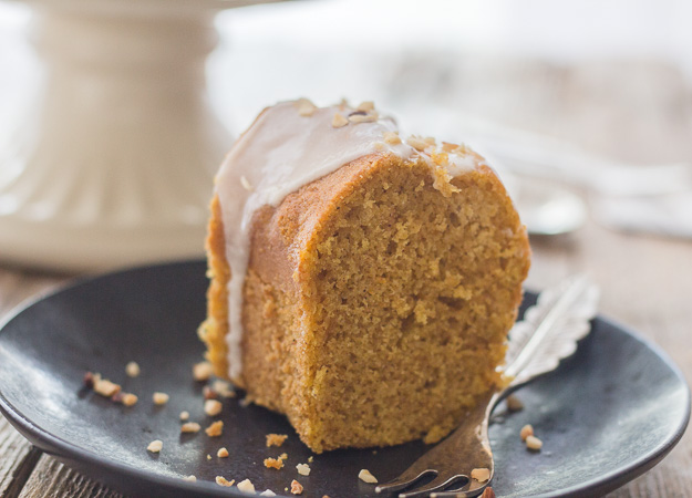 a slice of maple glazed pumpkin cinnamon cake on a black plate with a fork