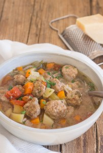 Italian meatball soup on a wooden board in a white bowl with a soup