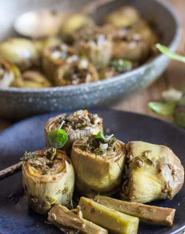 cooked roman artichokes in a pan and 3 on a plate