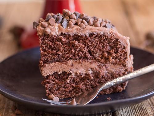 a slice of chocolate cake on a black plate