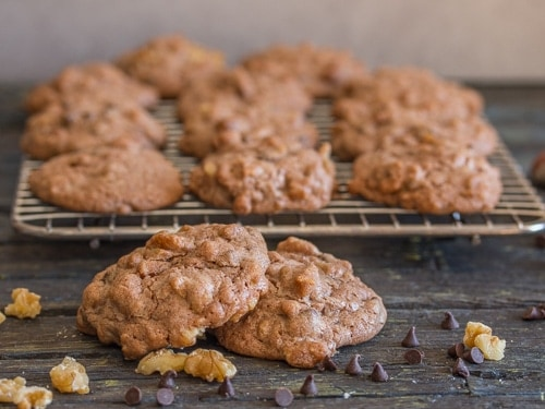 chocolate chip walnut cookies on a wire rack and 2 in front on a board
