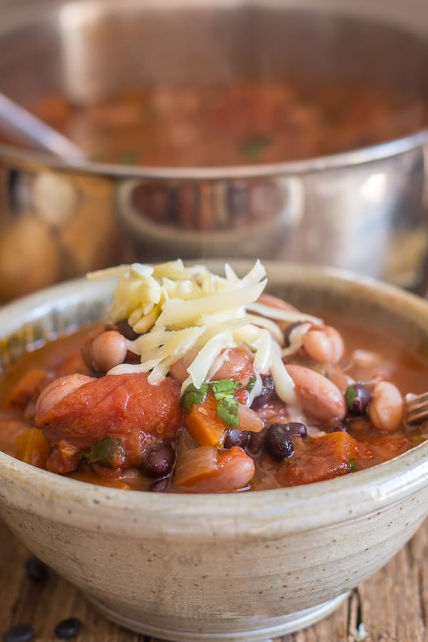 3 bean vegetarian chili in a bowl with shredded cheese on top