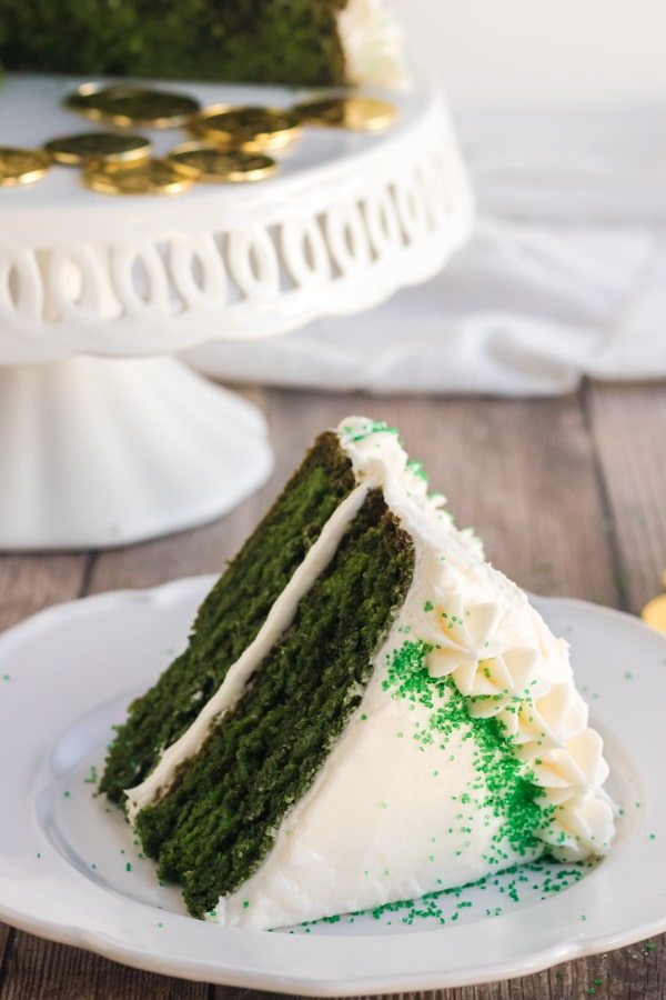 green velvet cake with a slice on a white plate