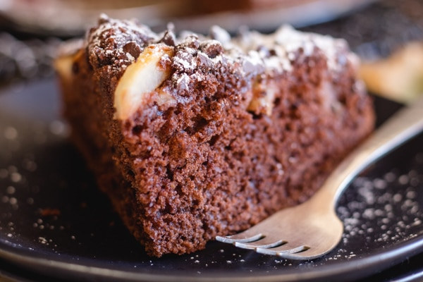 a slice of chocolate pear cake on a black plate