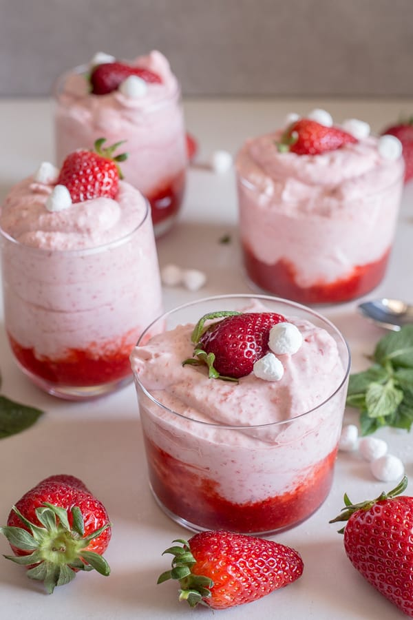 strawberry mousse in 4 glasses on a white board