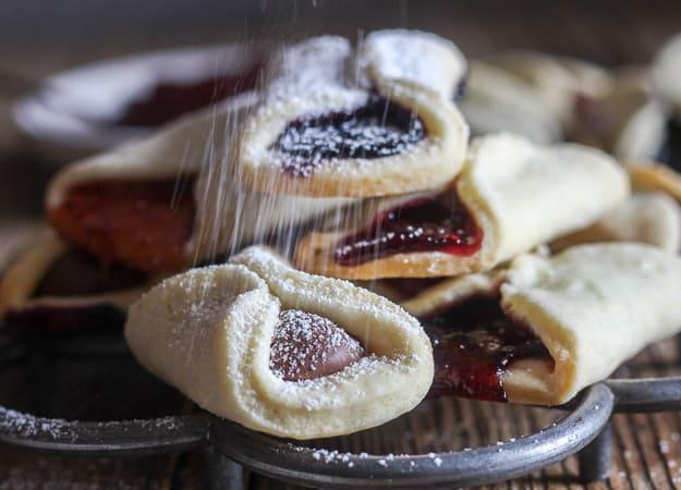 sprinkling icing sugar on pizzicati cookies
