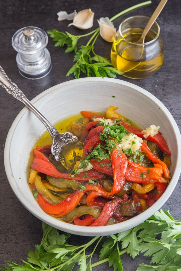 roasted peppers in a white bowl with the spices and garlic