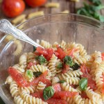 fresh tomato pasta salad in a glass bowl